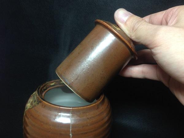 愛用の酒燗器で燗をつける。湯の入った陶器に、酒の入った徳利をスポッと収めるしくみ。熱くしすぎるとバランスが崩れるので注意しよう。