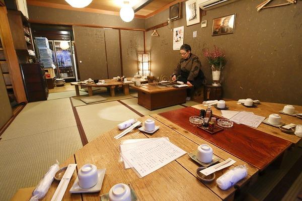 ↑串駒の二階。暖色の灯かりが穏やかに店内を照らす。手前のテーブルは、日本酒のタンクのフタを貰い受け、再利用したもの