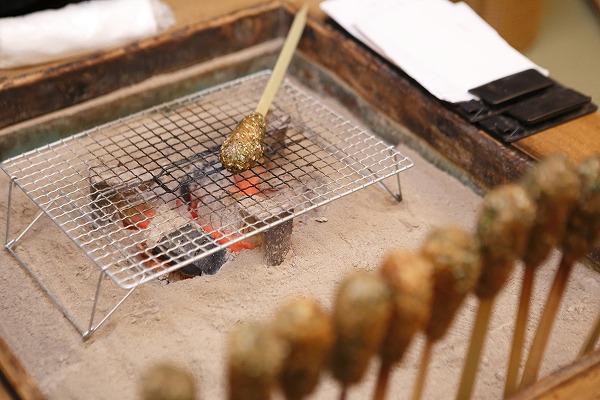 ↑雪江さんが関西火鉢で焼く名物のいしりもち(1本300円)。イカのはらわたを使った魚醤(魚を原料とする醤油)、「いしる」で炊いたもち米と飯米を半つぶしにして、青のりやゴマで味を整え、竹の棒に巻きつけて炙ったもの。関西火鉢に炭が入る冬場のみ味わえる