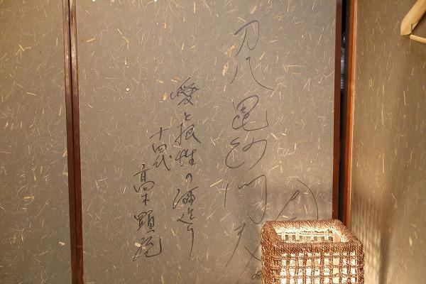 ↑同店2階の襖に書かれた高木顕統氏の一筆。「愛と根性の酒造り」とある