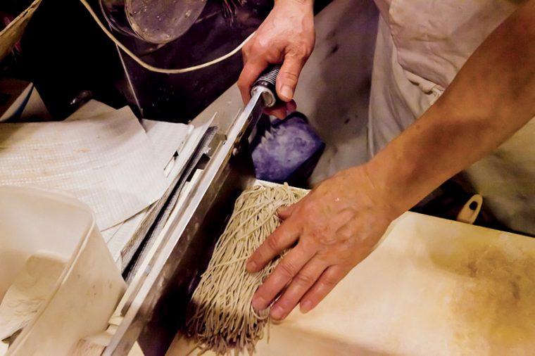 ↑店長は毎日朝と午後に、その日使う分のそばを包丁切りしている。細く長い麺にするためには、包丁切りの熟練した技が必要だ