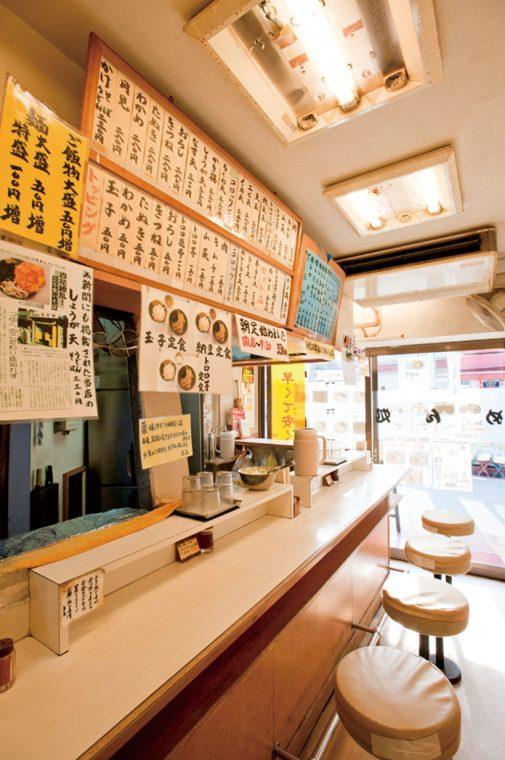 ↑小さな店内には椅子が7席ほど。カウンターの上に掲げられたメニューも豊富だ。なお、つゆが薄いと感じる客のために、卓上にはかえししょうゆも用意されている