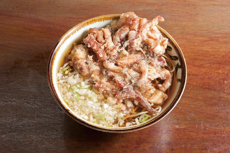 ↑かけそば+ゲソ天(430円)。丼を覆い尽くさんばかりのゲソは満足感あり。薬味のねぎをみじん切りにするのは珍しい