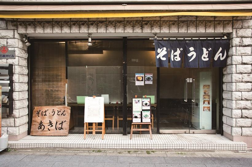↑店舗は昭和通り沿いに立つビルの1階に立地。店頭では、大きな木の板に書かれた「そば・うどん あきば」の看板が独特の存在感を放っている