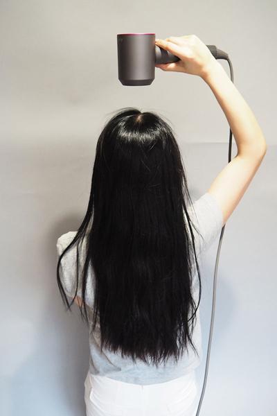 ノズルの方向を髪の流れに沿わせれば、強風モードでも髪はまったく飛び散りません。強い風が髪を抑えつけてくれるので、ブラシなしでも髪が広がりません
