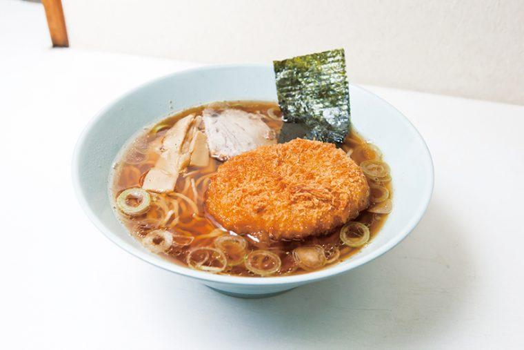 ↑コロッケラーメン(530円)。鶏と豚の骨でスープを取り、しょうゆ味の自家製だれと合わせた。細い縮れ麺はコロッケと不思議と合う