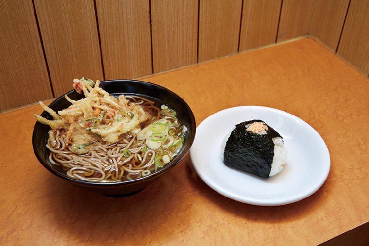 ↑かき揚げそば+おにぎり鮭(360円+125円)。つゆを吸ってほぐれる衣と野菜の味わいが絶妙。おにぎりと一緒に味わえばうまさ倍増だ