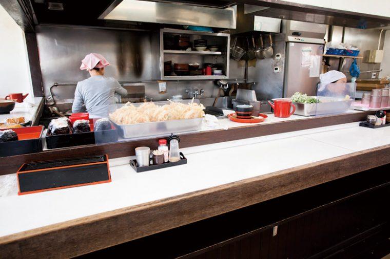 ↑厨房の中ではゆで、盛りつけなどを分業でこなす。カウンター上には天ぷら類のほか、おにぎり(1個100円)も並んでいる