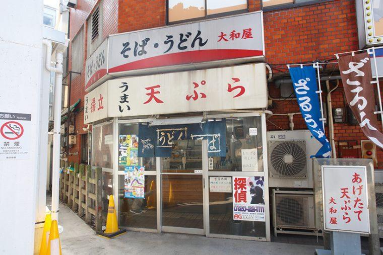 """↑大和屋は、駅の改札を出たらすぐそこ。白地に赤で「天ぷら」と書かれたシンプルな看板が""""うまそうなオーラ""""を放っている"""