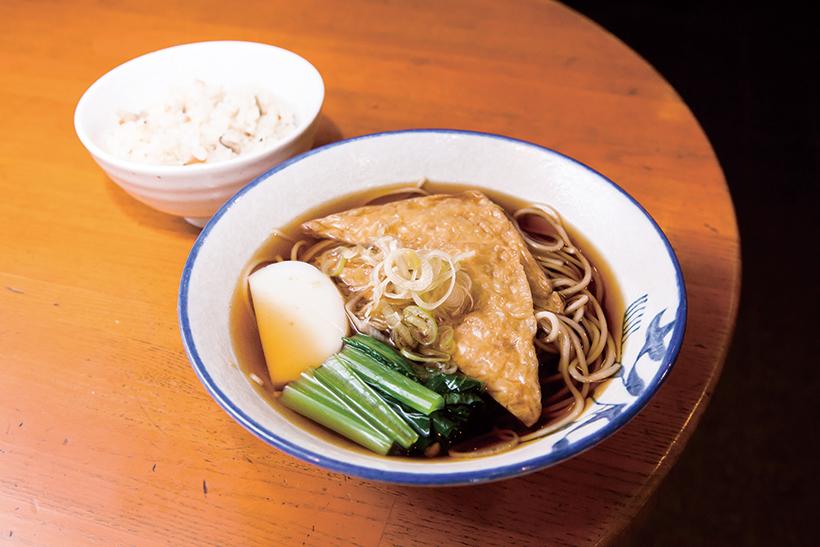 ↑甘過ぎない油揚げに小松菜、かまぼこの 彩りを加えた「きつねそば」。絶品かやくご飯 とのセットは店の人気メニューだ。