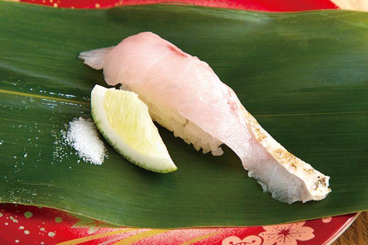 ↑のどぐろ/一貫(410円) 全国の漁港から築地に届く、鮮度抜群の高級魚「のどぐろ」を握りに。同店ではすだちと塩でいただく。濃厚な脂のうまみがすだちで引き立ち、爽やかなあと味を醸し出す