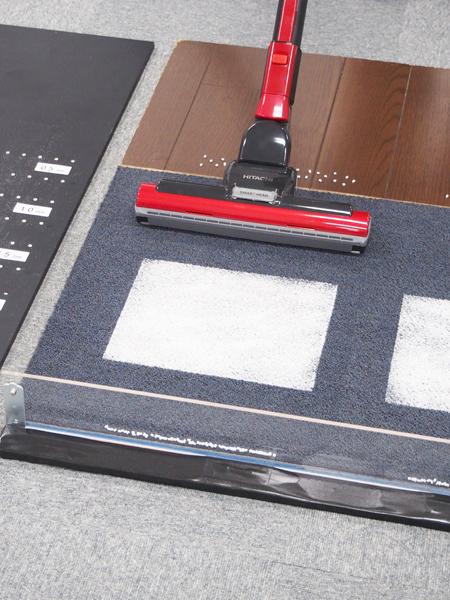 ↑カーペットの上に幅25cmの小麦粉、壁に見立てたアクリル板の際には粒々のペレットがずらり。フローリング部分にもペレットが撒かれています