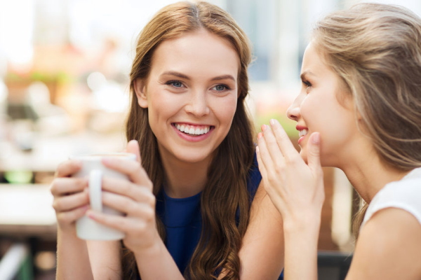 48092261 - people communication and friendship concept - smiling young women drinking coffee or tea and gossiping at outdoor cafe