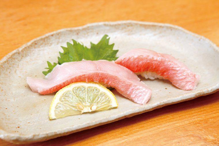 ↑地金目/二貫(518円) 肉厚で大ぶりにカットされた金目鯛は、食べ応え抜群。芳醇な脂の乗りだが、繊細な味わいも楽しめる。しょうゆは使わず、目の細かい塩とレモンで食べるのがオススメだ