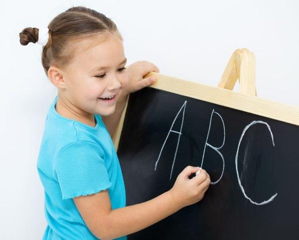 16336115 - cute little girl is writing letters on a blackboard in school