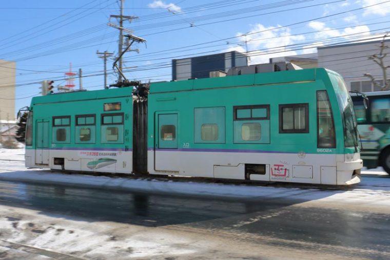 ↑上がグリーンに、下がホワイト、帯は紫色という北海道新幹線H5系カラーをまとった9600形電車が函館市内を疾走する