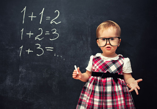 27584227 - baby girl pupil in glasses and chalk at a school board with arithmetic examples