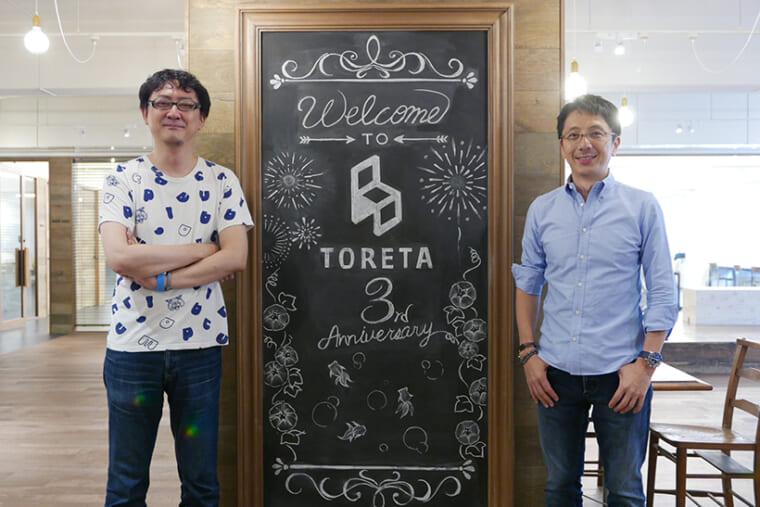 ↑サービス開始から3年目であることを知らせるブラックボードをはさんで。代表取締役 中村仁氏(右)と取締役COO 吉田健吾氏(左)