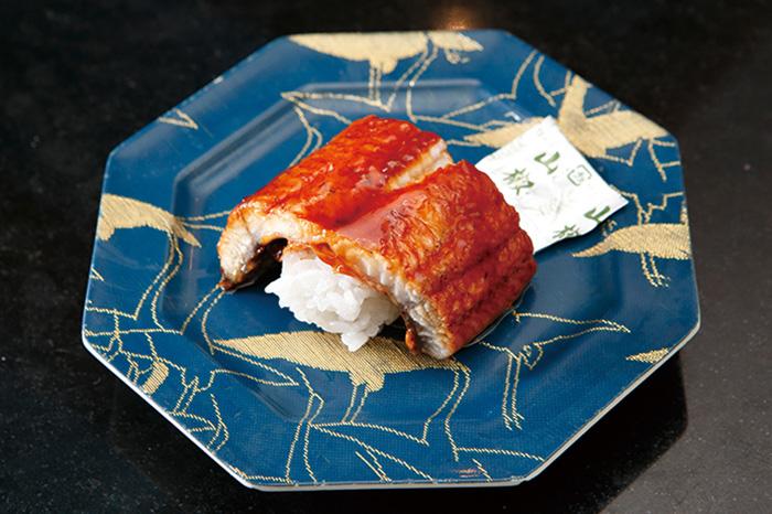 ↑うjなぎ/一貫(410円)  厚みのあるうなぎにタレを付けて 三度焼き。うなぎ独特の風味が濃厚 で、口の中にうまみがみるみる広が る。一貫でも十分食べ応えのある一 品。コストパフォーマンスは抜群だ。