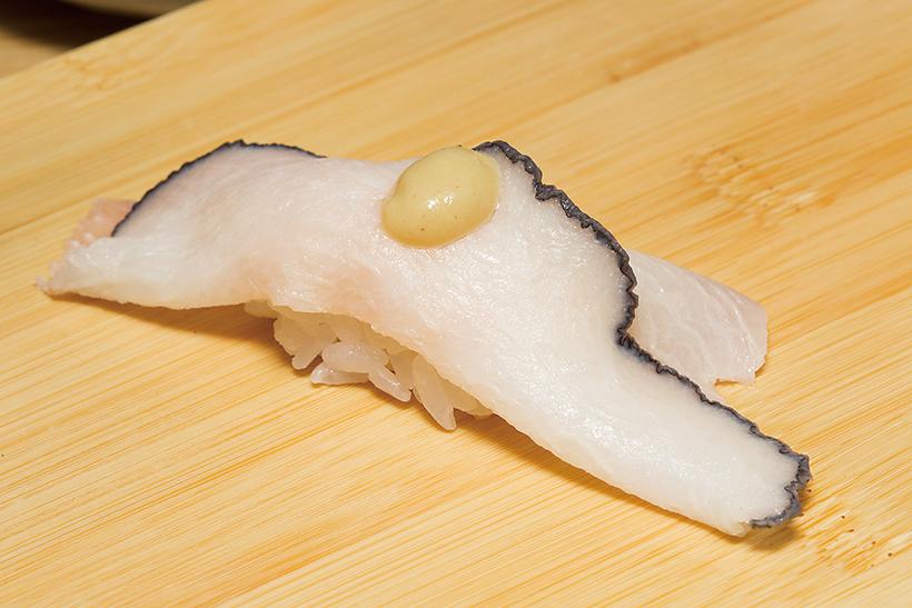 ↑鯨さずり/一貫(230円) くじらの舌を燻製(ベーコ ン)にして寿司ネタに。スモ ークされ凝縮した脂のうまみ がじわじわ広がる。トッピ ングの練りがらしが味のアクセントとなって、たまらなくうまい
