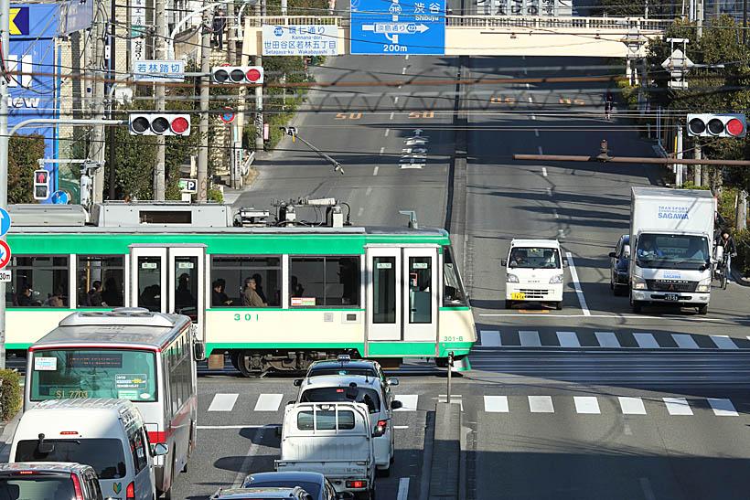 ↑世田谷線と環七通りが交差する若林踏切。若林駅のすぐ横を通る環七通りをゆっくりと電車が横切る