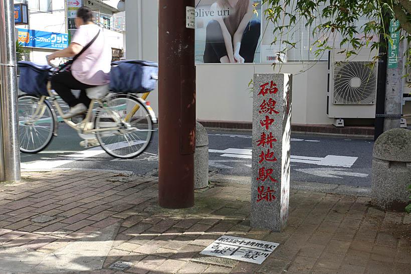 """↑ """"玉電""""砧線の中耕地駅跡に残る石碑。後ろの道路が元の線路跡だ。二子玉川駅から徒歩5分ほど"""