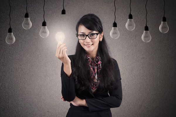 16548750 - beautiful asian businesswoman with glasses holds bright lightbulb