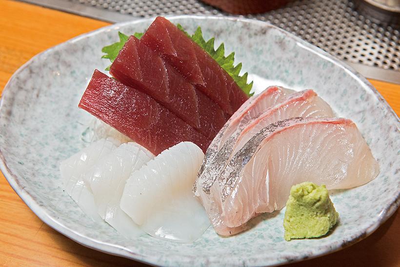 ↑刺身3点盛(900円) その日のオススメの魚を刺身三種盛りに。写真はまぐろの赤身とかんぱち、甲いかの子ども。甲いかの豊かな風味とうまみが印象的だ