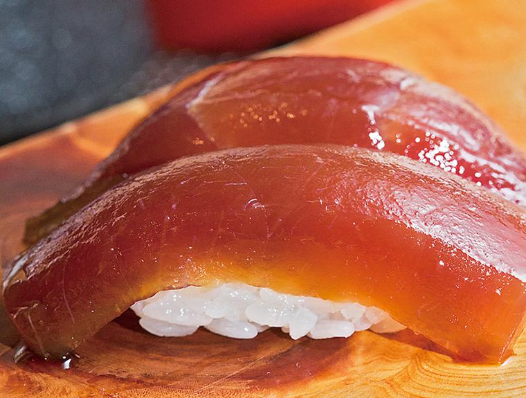 ↑づけまぐろ/二貫(250円) 江戸前寿司の伝統的な技法により、甘めの漬けだれに20分ほど漬けたづけまぐろ。色は十分に浸みているが、赤身の味がしっかり残っている。トロリとした食感が絶妙でおいしい。