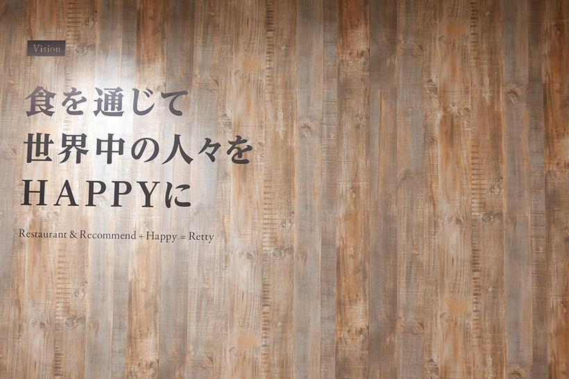 ↑オフィス入り口に掲げられた標語「食を通じて世界中の人々をHAPPYに」