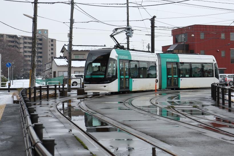 ↑奥田中学校前から富山駅北へ向け走る電車。左奥の遊歩道は以前、JR富山港線が走っていた路線跡だ