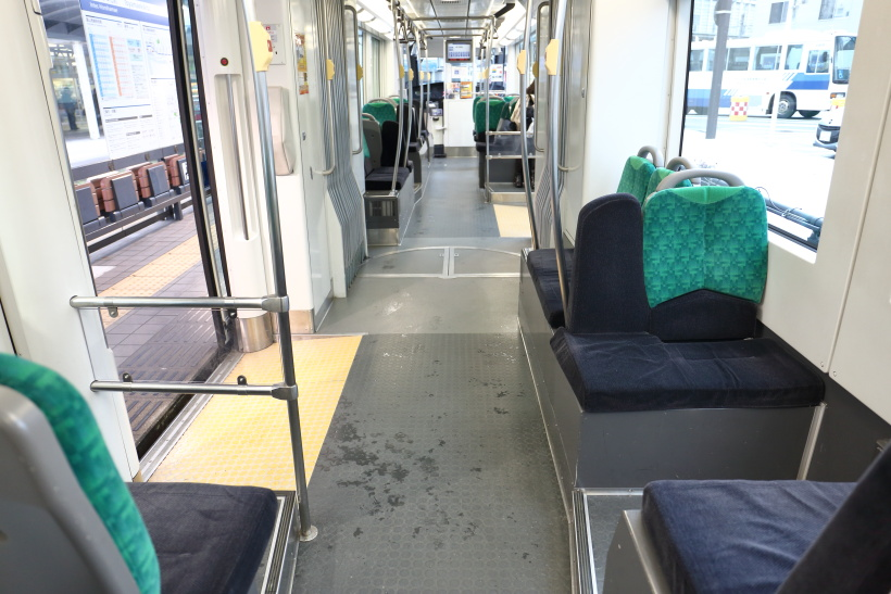 ↑車内はセミクロスシートで通路も広く造られている。通勤通学に利用する乗客も多い