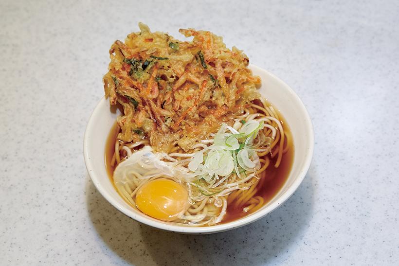 ↑天たまそば(440円) かき揚げは玉ねぎ、にんじん、桜えび入り。固めに揚げた衣に つゆと卵が絡んで、野菜の甘みが増す。