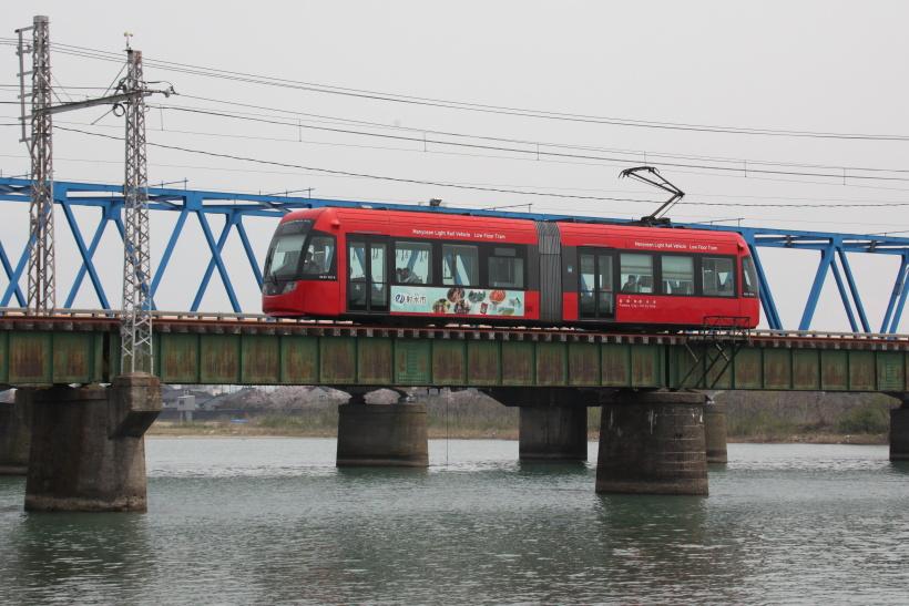 ↑庄川を渡るMLRV1000形電車。路面電車が大河に架かるガーダー橋を渡るというのも、ここならでは