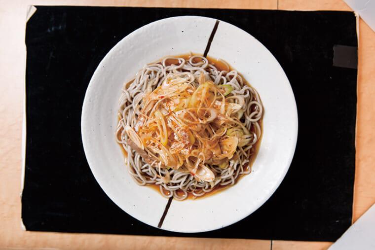 ↑冷しぴり辛ねぎそば(440円)。甘辛だれが絡むたっぷりの ねぎをそばと一緒に食べる ともうやみつき。「ぴり辛ね ぎそば」は温そばも人気だ。