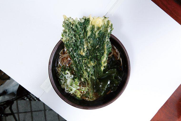 ↑春菊そば(430円)迫力満点な春菊天は、香り高く心地よい苦味がある。そばは適度なコシともっさり食感で、立ち食いそば 好きのツボにハマる。