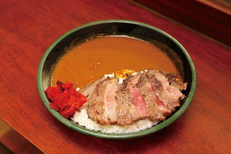 「ステーキカレー」はミディアムレアに焼いた牛肉をカレーにトッピング。ジュー シーな牛肉と、あとからくるルーの辛さのマッチングが見事だ。通常1100 円を火木土日は690 円で提供