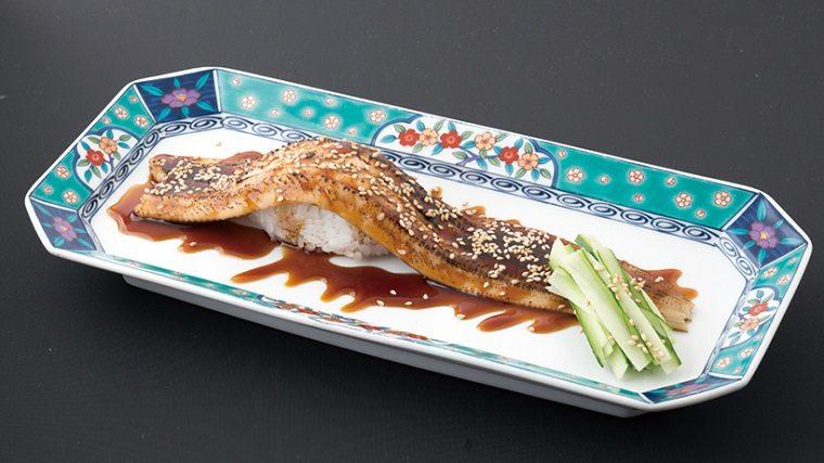 ↑一本穴子(702円) 堂々たる大きさの穴子。じ っくり煮上げてから、最後に 炙りを入れ、香ばしさを加え た。ツメがたっぷりかかって いて子どもでも食べやすい