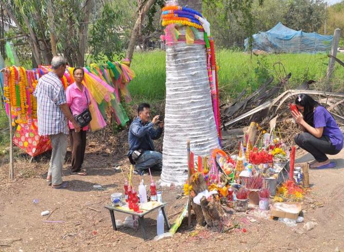 ↑ご神木には常に多くの人が群がり、お供え物が捧げられている