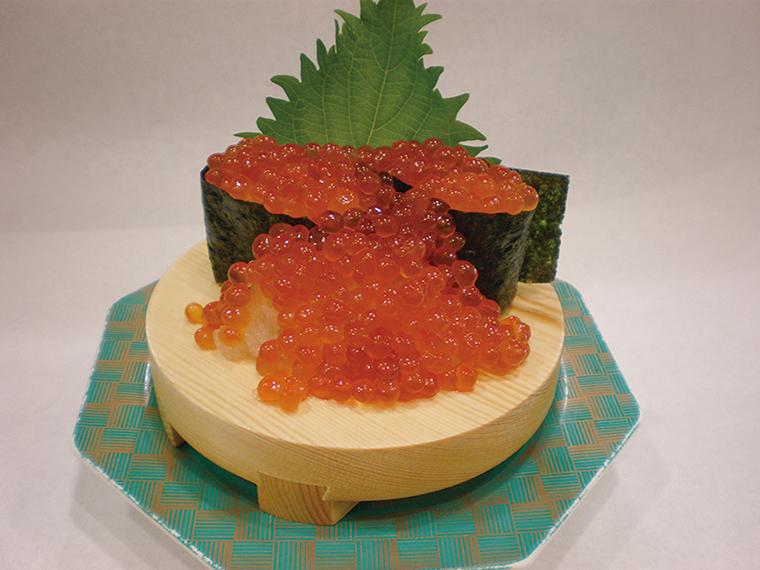 ↑いくら大漁こぼし/二貫(804円) 同店が発祥の大盛り こぼし寿司シリーズ のひとつ。プチプチ うまみが弾けるいく らを存分に味わえる