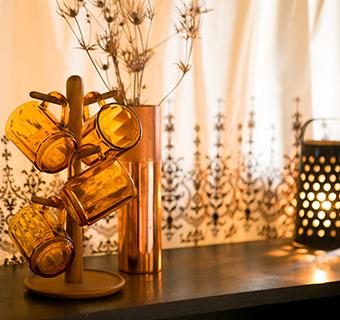 ↑秋らしい色の食器をカウンターテーブルに置いたコーディネート。くすんだ金属シェードの小さなランプをアクセントに