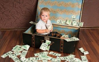 11471328 - cute little boy —ñs  sitting in a suitcase with the money