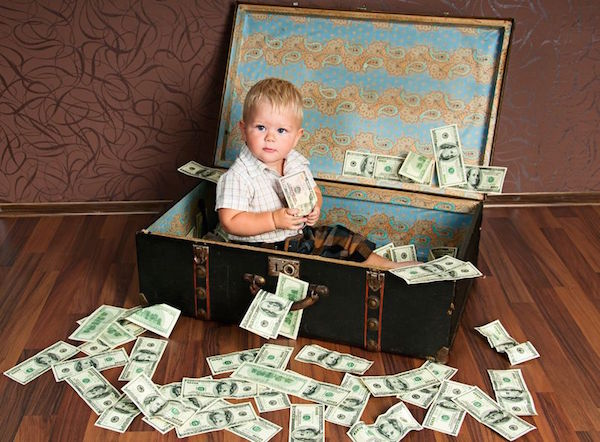 11471328 - cute little boy ?ns  sitting in a suitcase with the money