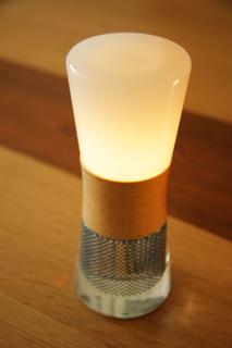 ↑ソーラーシステムで蓄電する砂時計をモチーフにしたLEDランタン「スフェラー®ランタン」。夜はベッドサイドの足元をほのかに灯してくれます。カラーはウォールナットと ハードメイプル(2種類)。H186mm x ø72.7mm。¥32,400(税込) http://www.sphelarpower.jp/
