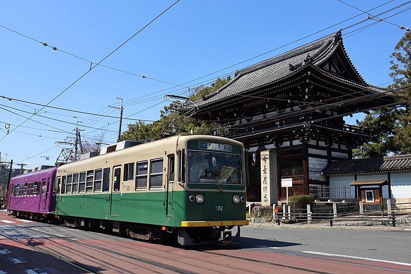 ↑愛嬌のある顔立ちのモボ501形が広隆寺の山門前の併用軌道を走る。嵐電ならではの光景だ