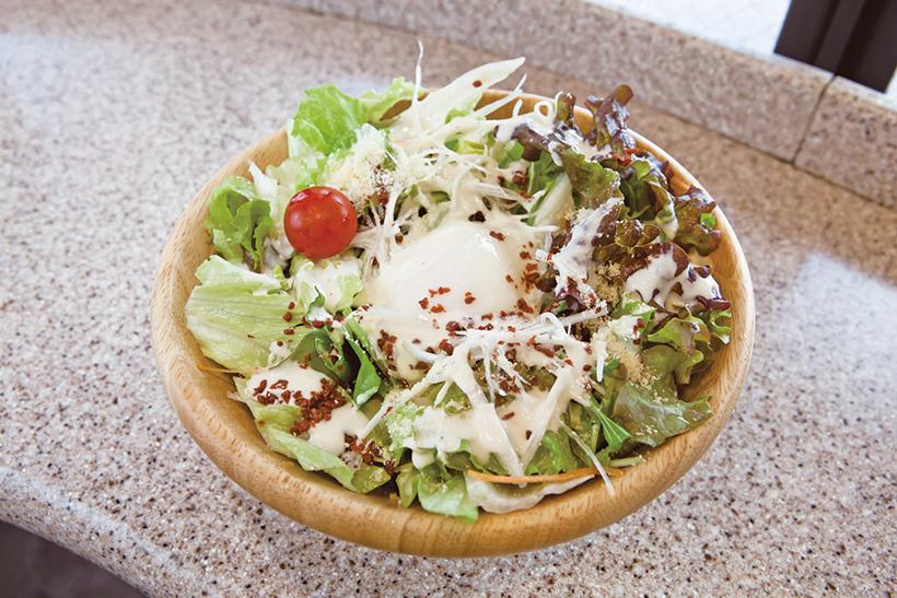 ↑しゃきしゃきサラダのぶっかけうどん(520円) うどんとたっぷりの野菜に、シーザーサラダドレッシングと粉チーズをかけて食べ る。めんつゆとドレッシング、温玉が一体化したうまみがすごい