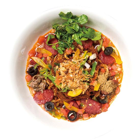↑ピザソバ 並(800円) サラミ、カイエンペッパー、チーズなど、独創的な具が満載。これらがトマトメインのソースと一体となり、太麺と絡んでピザのような味を生む