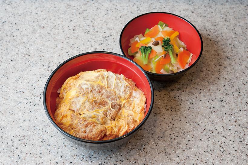 ↑一枚肉を使い、甘めの味つけで卵ふわふわのかつ丼も看板メニュー。ゆで野菜(右/ 100 円)を付ければ、よりヘルシーだ。