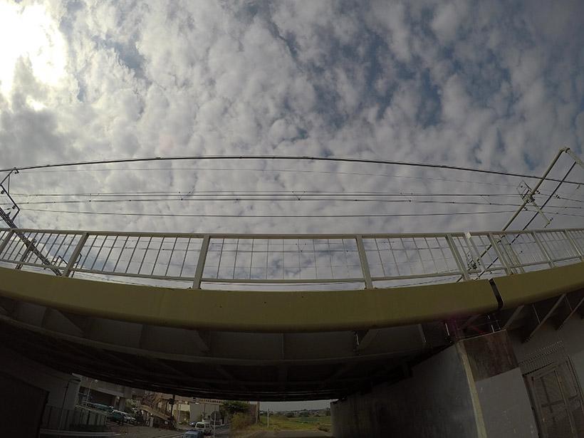 ↑「広角」モードで撮影。中心部の手すりや電線は直線ですが、中心から離れるにしたがって丸く歪み、下部にいたってはまるで高架が垂れ下がっているかのようです