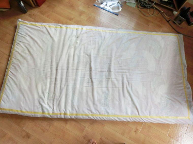 ↑自宅のせんべい布団で検体を採取。180×90cmの範囲をテープで囲い、そのなかをクリーナーでかけます